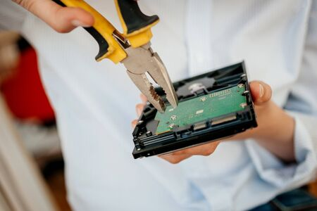 Female IT computer repair IT woman using yellow metal pliers to fix broken poor manufacture HDD disk drive with valuable stored data information open green board