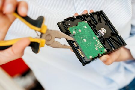 Hands IT computer repair engineer using yellow metal pliers to fix broken poor manufacture HDD disk drive with valuable stored data information