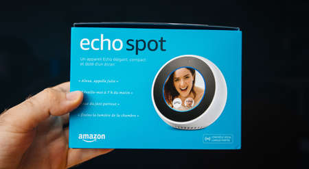 Paris, France - Jun 7, 2019: Man hand holding new Amazon Alexa Echo Spot with personal assistant Alexa brand of smart speakers developed by Amazon ready for unboxing