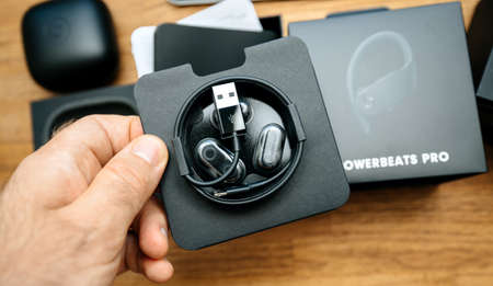 Paris, France - Jun 17, 2019: Man hand holding Eartips with four size options, Lightning to USB-A charging cable for apple Powerbeats Pro Beats by Dr Dre wireless headphones during unboxing Archivio Fotografico - 150564596