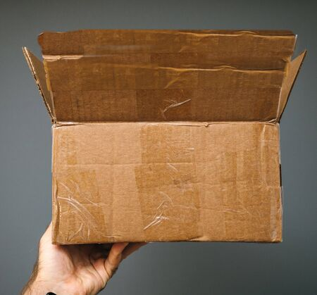 Man hand holding open cardboard box after before unboxing with protective paper carton
