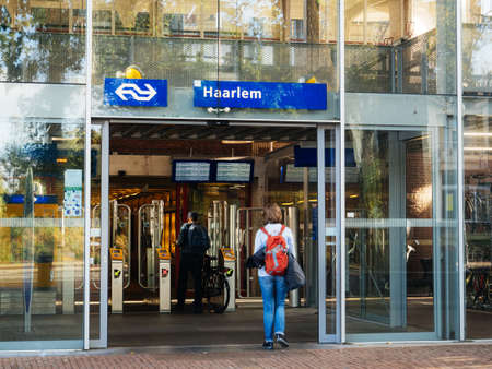 Haarlem, Netherlands - Aug 20, 2018: Haarlem central train station entrance from Kennemerplein 6 street with woman wearing red backpack entering through door Editoriali