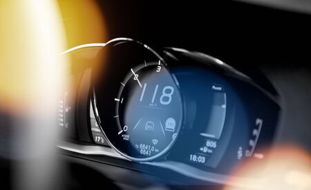 New modern luxury sport car digital dashboard showing driving data and current speed as well traffic signs recognition beautiful blue and yellow sunlight flare.