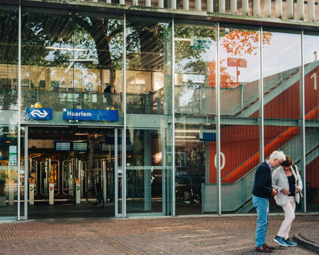 Haarlem, Netherlands - Aug 20, 2018: Haarlem central train station entrance from Kennemerplein 6 street with adult couple near glass facade Editoriali