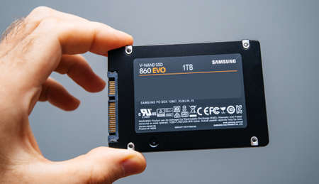 Paris, France - May 18, 2019: man hand holding new SSD Solid state drive disk from Samsung model 860 EVO 1 tb fastest flash media disk - gray background