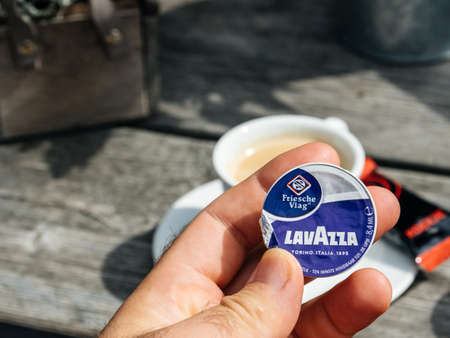 Hoenderloo, Netherlands - Aug 17, 2018: Man hand holding Lavazza coffee milk pack small coffee creamer with cup on the table Editorial