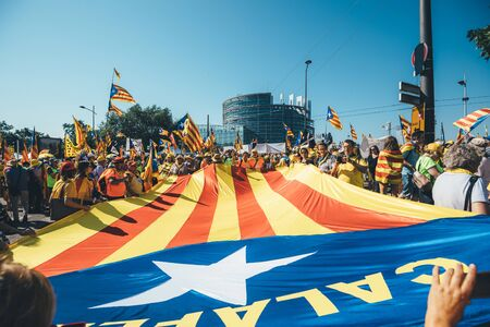 Strasbourg, France - Jul 2 2019: People holding immense Estelada Catalan separatist flags demonstration protest front of EU European Parliament against exclusion of three Catalan elected MEPs