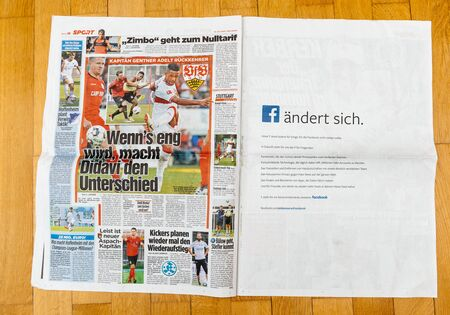 PARIS, FRANCE - JUL 16, 2018: Man reading Die Bild German newspaper announcing France champion title French national football team won their FIFA World Cup 2018 - facebook advertising opposite page