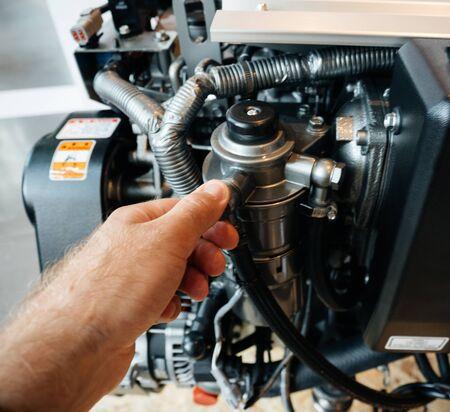 Male hand repairing demonstrating the new 4-stroke, vertical, water-cooled diesel engine powerboat engine