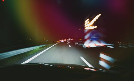 Driver POV fast transportation commuting the dark highway with accident roadworks and light flashing arrow Archivio Fotografico