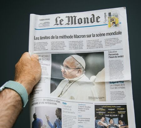 Paris, France - Jun 7, 2018: Man hand holding reading Le Monde newspaper magazine featuring Pope Francis on the cover