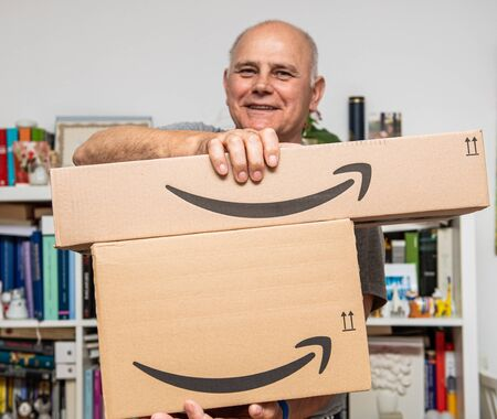Paris, France - Jul 10, 2019: Front view of happy smiling senior male holding delivering two Amazon Prime parcels