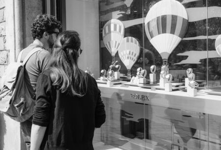 Barcelona, Spain - June 1, 2018: Rear view of young couple shopping for modern new last collection of luxury wrist Swiss watch manufactured by Rolex model - black and white image