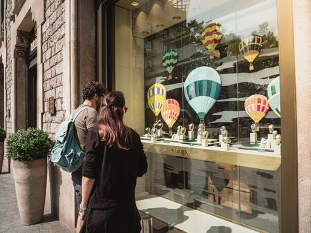 Barcelona, Spain - June 1, 2018: Tourist Couple shopping for modern new last collection of luxury wrist Swiss watch manufactured by Rolex Spanish holiday shopping Editorial