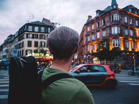 Rear view of unrecognizable adult man with heat looking at the building intersection deciding where to go next in the big French city of Strasbourg Imagens