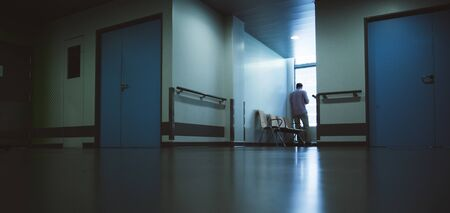 Low angle view of lonely patient in full length in modern hospital waiting lobby room waiting near the window impatiently as he waits for good or bad news from his doctor