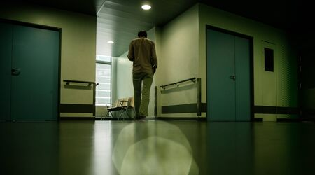 Low angle view of lonely patient in full length in modern hospital waiting lobby room walking impatiently as he waits for good or bad news from his doctor