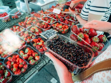 Side view of french woman shopping for fresh currant and strawberries on local farmers market - organic bio food harvested in French villages