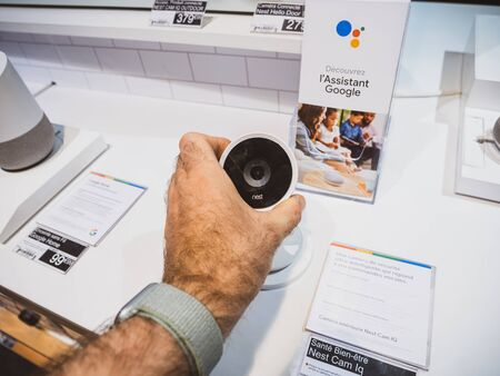 Paris, France - Jul 25, 2019: Man hand admiring looking at the Nest Cam IQ new premium model of Nest Cam Indoor. It features a 4K camera sensor with HDR