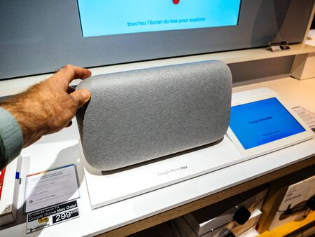 Paris, France - Jul 25, 2019: Man hand holding inside electronics store on Google Max larger version with stereo speakers including two tweeters and subwoofers, an audio connector, and a USB Type-C co