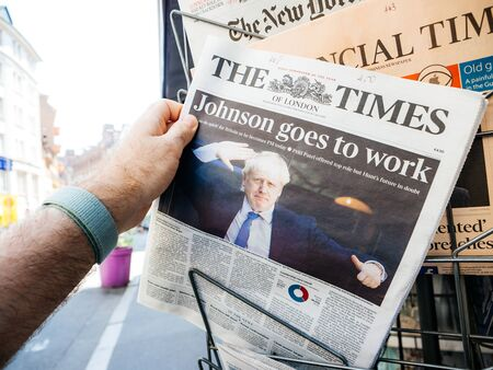 Paris, France - Jul 24, 2019: Man taking from press stand The Times Newspaper with Boris Johnson on cover page as he becomes UK United Kingdom Prime Minister and title Johnson goes to work