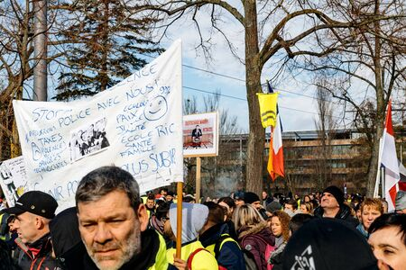 STRASBOURG, FRANCE - FEB 02, 2018: People marching during protest of Gilets Jaunes Yellow Vest manifestation anti-government demonstrations placards against Emmanuel Macron