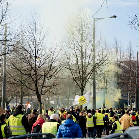 STRASBOURG, FRANCE - FEB 02, 2018: People marching during protest of Gilets Jaunes Yellow Vest manifestation anti-government demonstrations waving green smoke grenade