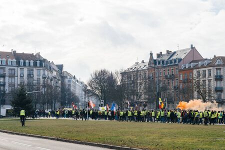 STRASBOURG, FRANCE - FEB 02, 2018: People marching during protest of Gilets Jaunes Yellow Vest manifestation anti-government demonstrations on Place de Bordeaux