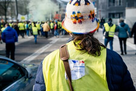 STRASBOURG, FRANCE - FEB 02, 2018: People marching during protest of Gilets Jaunes Yellow Vest manifestation anti-government demonstrations - man with Carte Electorale voting card destroyed