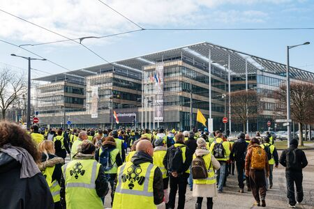 STRASBOURG, FRANCE - FEB 02, 2018: People marching during protest of Gilets Jaunes Yellow Vest manifestation anti-government demonstrations in front of Region Grand Est building