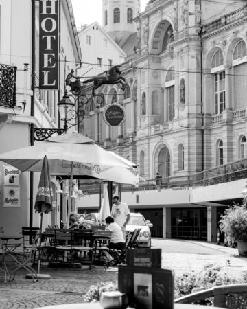 Baden-Baden, Germany - Jul 7, 2019: Outdoor terrace with customers people at the hotel with Bader Taverna and Friedrichsbad Baden-Baden, famous thermal baths - black and white