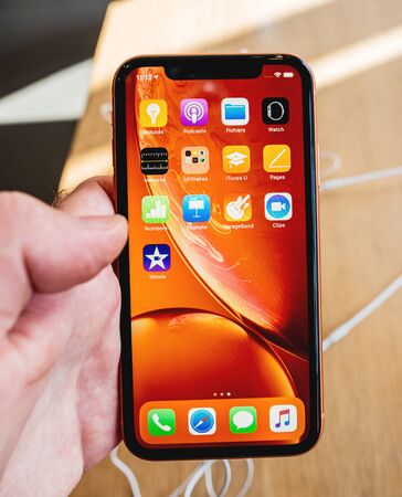 Paris, France - Oct 26, 2018: Man palm holding latest red iPhone XR smartphone during launch day manufactured by Apple Computers
