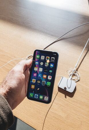 Paris, France - Oct 26, 2018: Man hand holding latest iPhone XR smartphone during launch day manufactured by Apple Computers