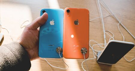 Paris, France - Oct 26, 2018: POV of man hand holding two latest iPhone XR smartphone during launch day manufactured by Apple Computers
