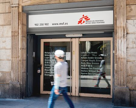 Barcelona, Spain - Jun 1, 2018: Silhouette of young man walking in front of Doctors Without Borders Medecins Sans Frontieres headquarter the international humanitarian medical non-governmental organisation