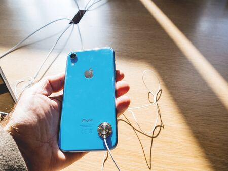 Paris, France - Oct 26, 2018: Man hand holding latest blue iPhone XR smartphone during launch day manufactured by Apple Computers admiring icon on rear part