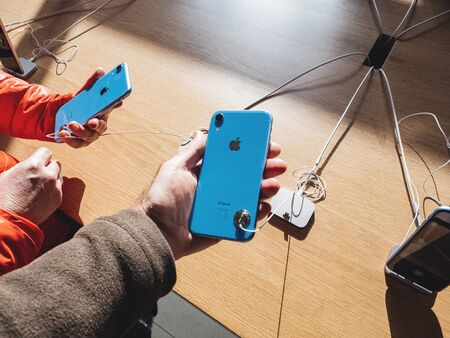 Paris, France - Oct 26, 2018: Man and woman hand holding two latest blue with silver logotype iPhone XR smartphone during launch day manufactured by Apple Computers