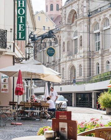 Baden-Baden, Germany - Jul 7, 2019: Outdoor terrace with customers people at the hotel with Bader Taverna and Friedrichsbad Baden-Baden, famous thermal baths