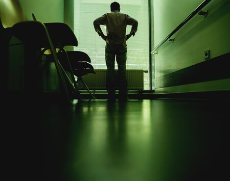 Low angle view of lonely patient in full length in modern hospital waiting lobby room uin front of window hands on hips as he waits for good or bad news from his doctor Banque d'images