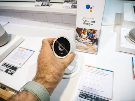 Paris, France - Jul 25, 2019: Man hand looking at the Nest Cam IQ new premium model of Nest Cam Indoor. It features a 4K camera sensor with HDR Редакционное