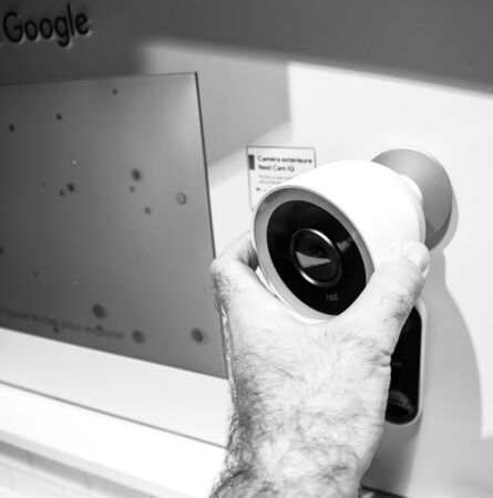 Paris, France - Jul 25, 2019: Man hand looking at the Nest Cam IQ on wall new premium model of Nest Cam Indoor featuring a 4K camera sensor with HDR