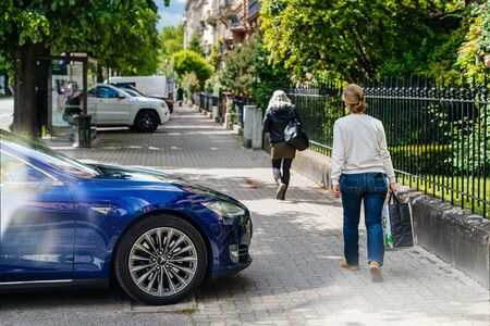 Strasbourg, France - May 19, 2016: People walking near modern luxury Tesla Model S 90D electric supercar parked in beautiful blue color parked on the French street Redakční