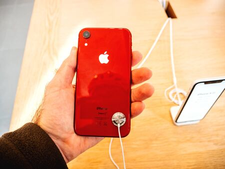 Paris, France - Oct 26, 2018: Man hand holding latest red iPhone XR smartphone during launch day manufactured by Apple Computers admiring on rear part