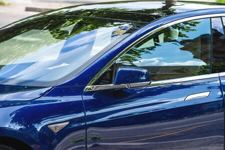 Strasbourg, France - May 19, 2016: Detail of rear view mirror of modern luxury Tesla Model S 90D electric supercar in beautiful blue color parked on the French street
