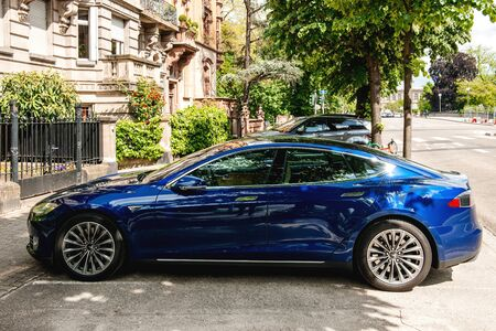Strasbourg, France - May 19, 2016: Side view of modern luxury Tesla Model S 90D electric supercar in beautiful blue color parked on the French street with beautiful architecture buildings