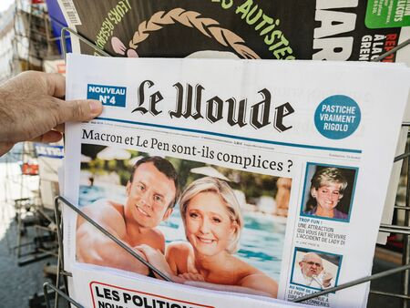 Paris, France - Jul 24, 2019: Man hand holding satirical Le Woude newspaper at French press kiosk with collage of French President Emmanuel Macron and Marine Le Pen Redakční