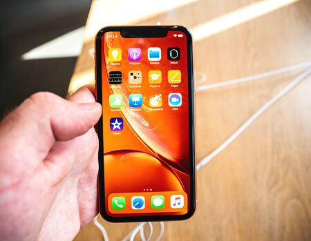 Paris, France - Oct 26, 2018: Man hand holding latest iPhone XR smartphone during launch day manufactured by Apple Computers red home scree with apps