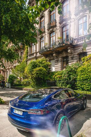 Strasbourg, France - May 19, 2016: Rear elevated view of modern luxury Tesla Model S 90D electric supercar in beautiful blue color parked on the French street near luxury apartment house building