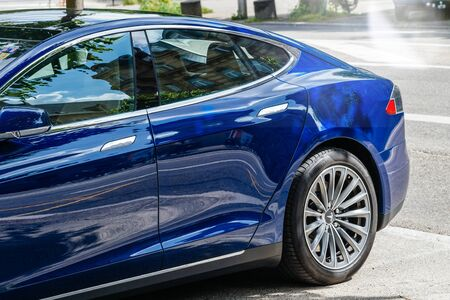 Strasbourg, France - May 19, 2016: Side view rear part of modern luxury Tesla Model S 90D electric supercar in beautiful blue color parked on the French street