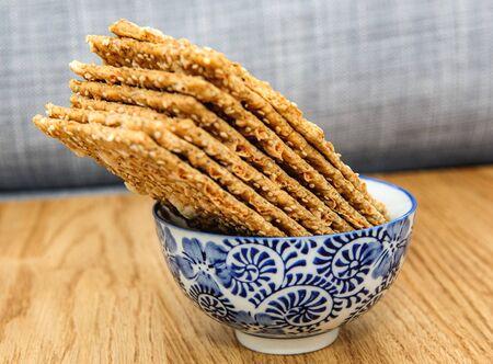 Side view of bio delicious crispbread bread in japanese blue porcelain bowl on wooden oak table - delicious bio organic food